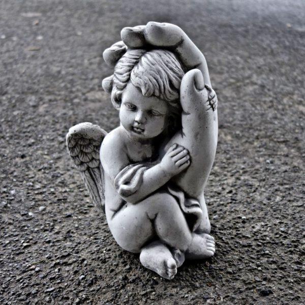 Engel leunend tegen hand